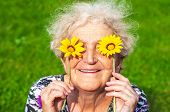 A Cheerful Grandmother Looks At The Flower Look Of Yellow Daisies. Womens Health, Skin Care, Eyesig poster