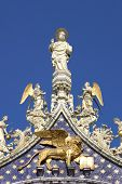 Vertical oriented image of St. Mark sculpture on the rooftop of San Marco Basilica against blue sky
