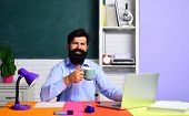 Friendly Teacher In Classroom Near Blackboard Desk. Teacher Is Skilled Leader. Education And Learnin poster