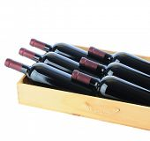 Closeup of six Cabernet Sauvignon wine bottles in a wooden crate. Square format isolated on white.