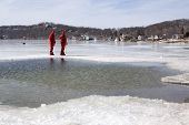 SPARTA, NJ - FEB 20: Two members of the Sparta Volunteer Fire Dept in orange immersion suits stand n