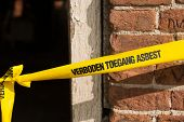 Yellow ribbon with Dutch text forbidden asbestos