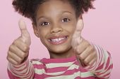 Closeup portrait of a happy girl giving double thumbs up on pink background