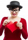 Постер, плакат: Красивые и смешные ботаник девочка рвать бумаги сердца изолированные на белом фоне