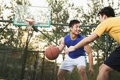stock photo of offensive  - Two street basketball players on the basketball court - JPG