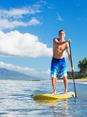 Young Attractive Mann on Stand Up Paddle Board, SUP, in the Blue Waters off Hawaii, Active Life Concept