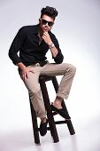 young fashion man sitting on a chair and holding his hand at his chin while looking pensively at the