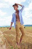 full length portrait of a young casual man posing outdoor with his shirt unbuttoned and his hand on