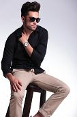 young fashion man sitting on a chair and looking away while holding his hand tucked in his shirt, at