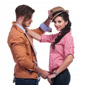 side view of a young casual couple playing while the woman looks into the camera and the man takes off her hat and belt. on white background