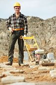 stock photo of vibration plate  - builder worker at outdoor sand ground compaction with vibration plate compactor machine before concrete filling - JPG