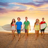 foto of board-walk  - Surfers teen boys and girls group walking on beach at sunshine sunset back light - JPG