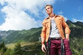 young casual man standing in the mountains, holding a hand in his pocket and looking away from the c