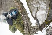 paintball extreme sport player in protective mask and comouflage clothing with marker gun at winter