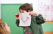 foto of daycare  - Playful little boy holding paper with smile drawn on it while looking at girl in art class - JPG