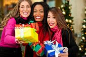 Group of three women - white, black and Asian - with Christmas presents in a shopping mall in front