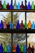 Colorful glass bottles on windowsill