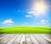 Green field under blue sky. Wood floor