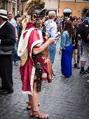 Roman soldier sending a text message at the Trevi Fountain in full regalia