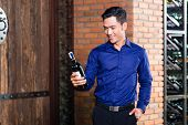 Asian man holding bottle of wine