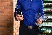 Midsection view of man holding bottle of wine and two wine glasses