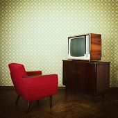 Vintage room with two old fashioned armchair and retro tv over obsolete wallpaper. Toned