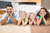Happy siblings lying on the rug posing with their parents at home in living room