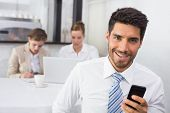 Businessman text messaging with colleagues in meeting behind at office desk