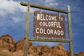 'Welcome to colorful Colorado' roadside wooden sign with red sandstone cliff in background.