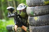 pic of paintball  - paintball player in protective uniform and mask aiming marker gun in summer - JPG