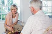 Smiling woman playing chess with man at home