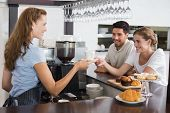 Side view of a friendly female waiter giving coffee to a couple at the coffee shop
