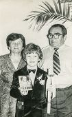 LODZ, POLAND, SEVENTIES - Vintage photo of little boy with his grandparents at his First Communion