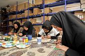 ESFAHAN, IRAN - DECEMBER 01, 2007:  Muslim women artists in black headscarfs paint traditional Persian miniature