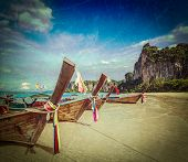 Vintage retro hipster style travel image of Long tail boats on tropical beach (Railay beach) in Thai