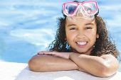 A cute happy young interracial African American girl child relaxing on the side of a swimming pool s