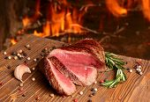 Beef Steak On A Wooden Table On A Background Of Fire