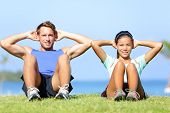 Sit ups - fitness couple exercising sit up outside in grass in summer. Fit happy people working out