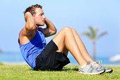 Sit-ups - fitness man training sit up outside in grass in summer. Fit male athlete working out cross