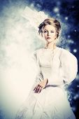 Portrait of a beautiful fashion model in the refined white dress and elegant hat. Snow queen. Winter