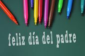 feliz dia del padre, happy fathers day written in spanish in a chalkboard, and some felt-tip pens of different colors