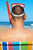 a man wearing a diving mask and a snorkel seated in a deckchair on the beach with the text happy summer written in his back as a tan mark