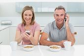 Couple using cell phones while having breakfast in the kitchen at home