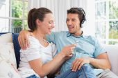 Relaxed young couple listening music with mobile phone on couch at home