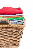 stock photo of neat  - Wicker basket of clean fresh laundry filled with neatly folded clean washed clothes awaiting ironing close up side view isolated on white - JPG