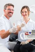Successful Dentists in their surgery looking at the viewer standing side by side