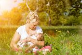 stock photo of breastfeeding  - Mother breastfeeding her baby on a great sunny day in a meadow - JPG