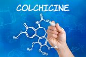 Hand with pen drawing the chemical formula of colchicine
