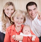 Family generation portrait, beautiful elegant grand mother holding on hands newborn granddaughter, m