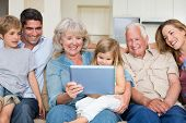 stock photo of granddaughter  - Happy multigeneration family using digital tablet at home - JPG